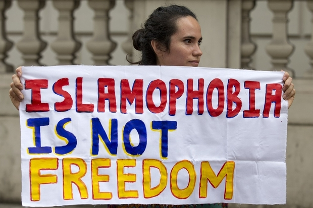"A protester holds a sign which reads "" Islamophobia is not freedom"" outside the French Embassy in London on August 25, 2016 during a ""Wear what you want beach party"" to demonstrate against the ban on Burkinis on French beaches and to show solidarity with Muslim women. French Interior Minister Bernard Cazeneuve warned Wednesday against stigmatising Muslims, as a furore over the banning of burkinis grew with the emergence of pictures showing police surrounding a veiled woman on a beach.  Dozens of French towns and villages, mostly on the Cote d'Azur, have banned beachwear that ""conspicuously"" shows a person's religion -- a measure aimed at the full-body Islamic swimsuit but which has also been used against women wearing long clothes and a headscarf. / AFP PHOTO / JUSTIN TALLIS"
